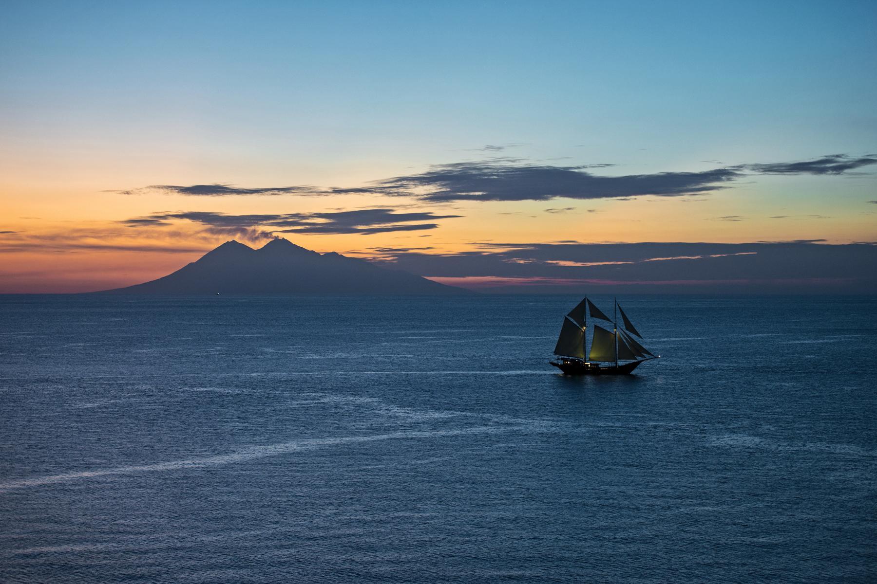 Das Segelschiff Amandira von Aman Cruises auf offener See im Dämmerlicht