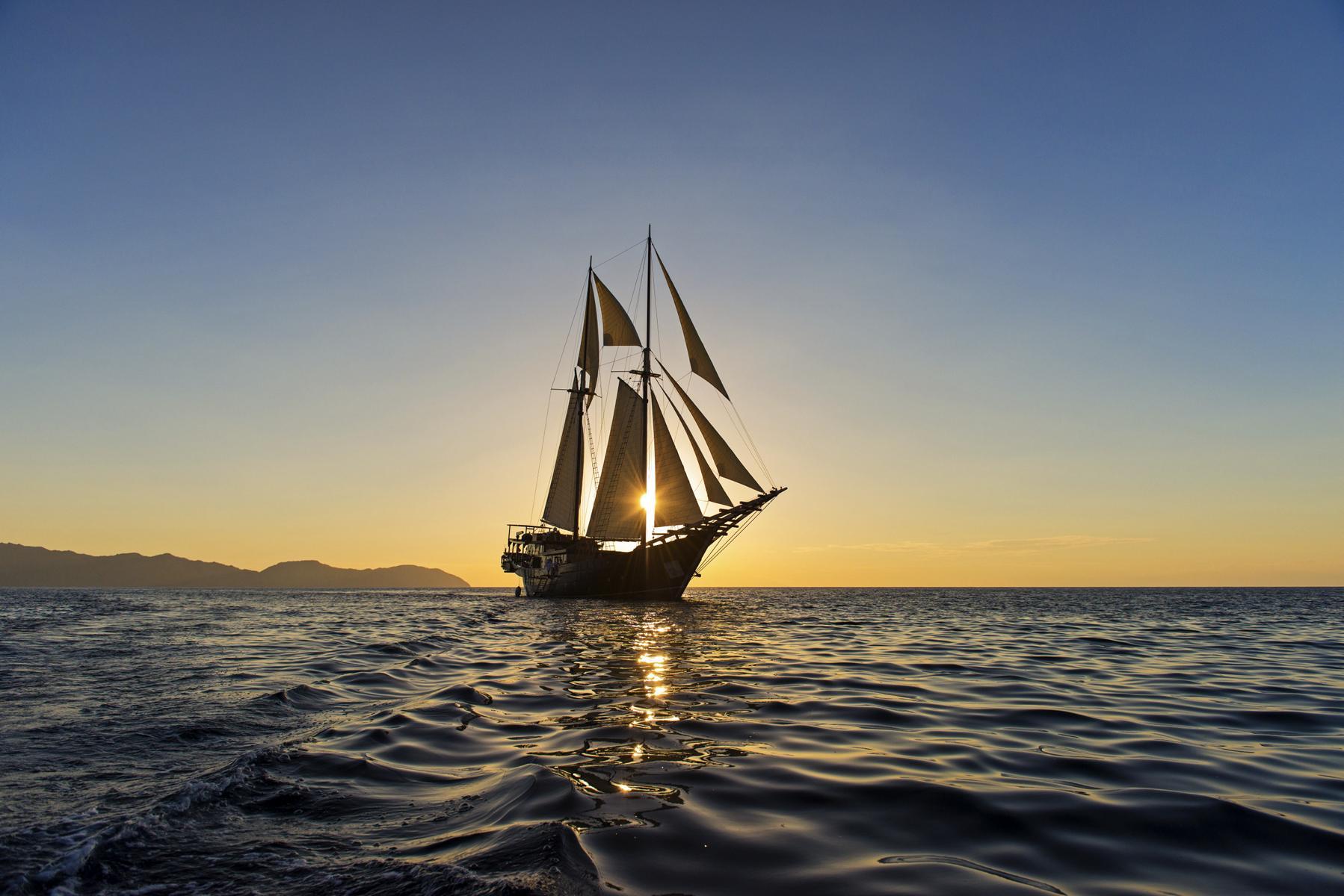 Das Segelschiff Amandira von Aman Cruises im Dämmerlicht auf offener See