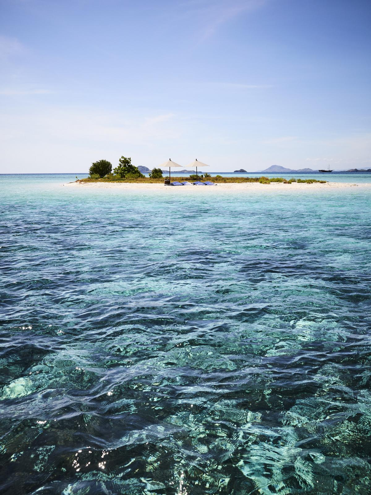 Kleine private Insel mit Sonnenliegen im türkisblauen Meer vor Indonesien bei einer Reise mit der Amandira von Aman Cruises