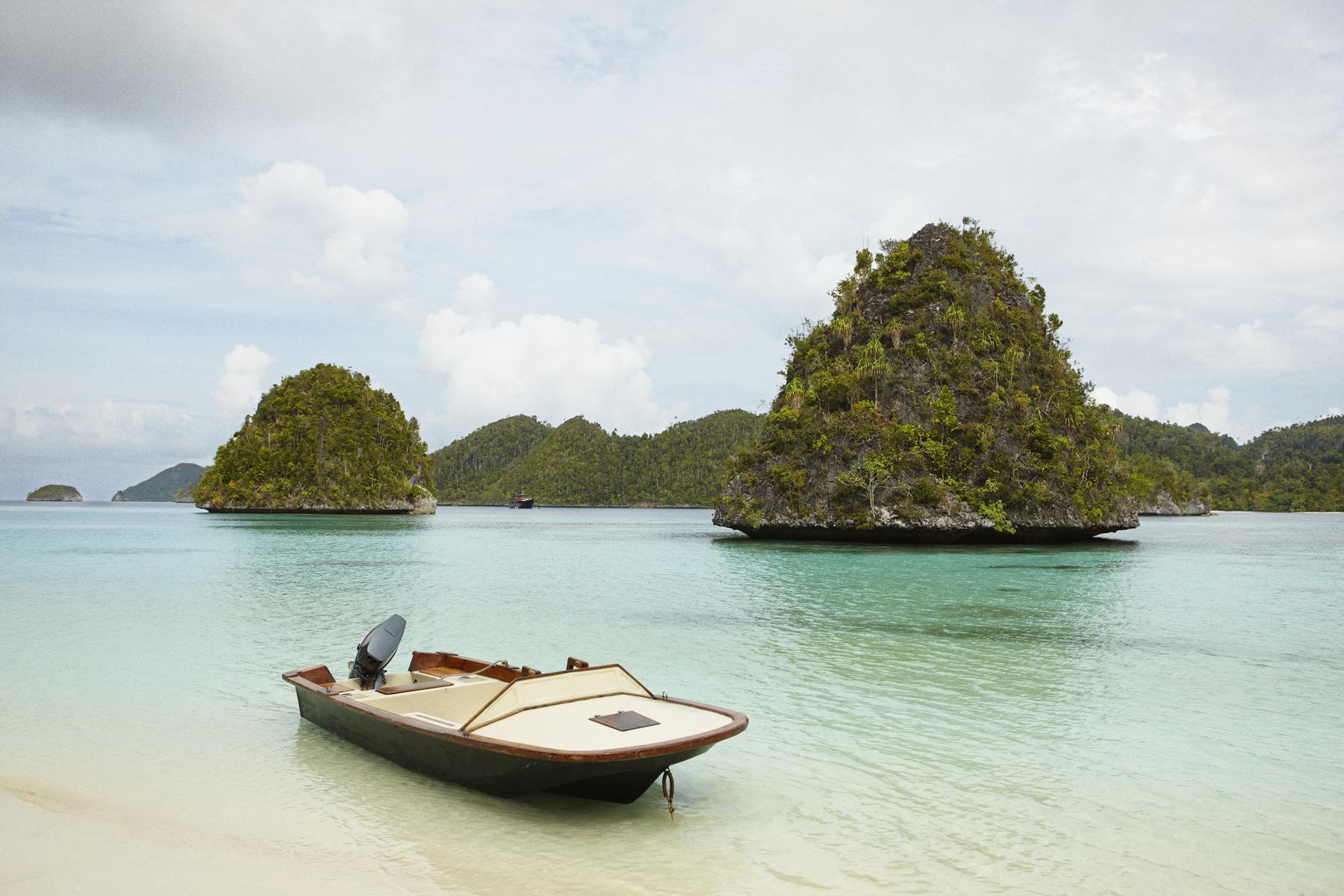 Ruderboot am Strand von Indonesien auf einer Reise mit der Amanikan von Aman Cruises