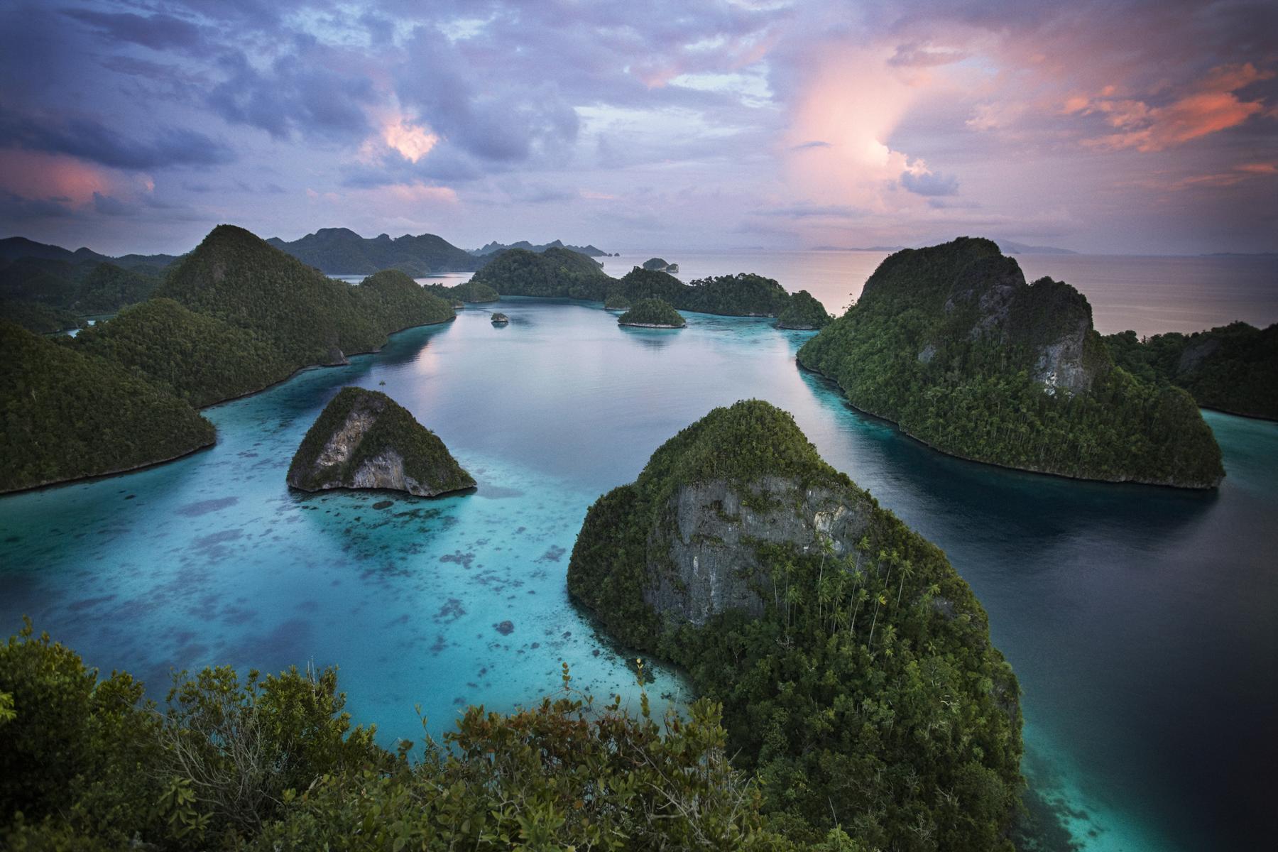 Felsige Küstengewässer Indonesiens im Dämmerlicht bei einer Reise mit der Amanikan von Aman Cruises