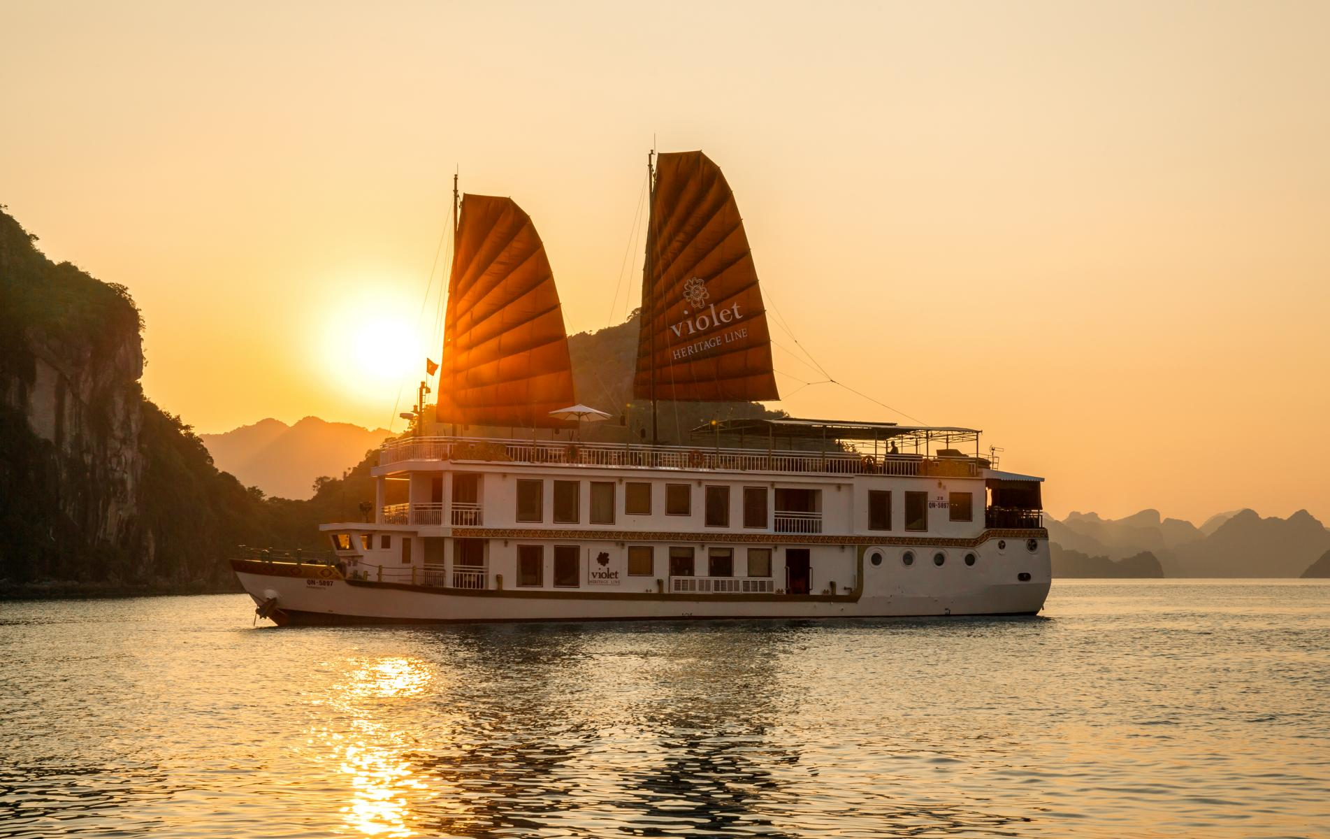 Die Violet der Heritage Line in der Halong Bucht im Sonnenuntergang