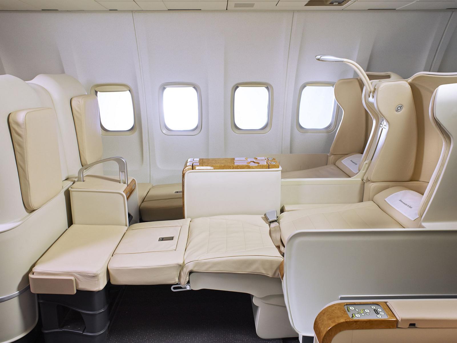 Innenraum mit flach gelegten Sitzen im Privatjet von Abercrombie & Kent