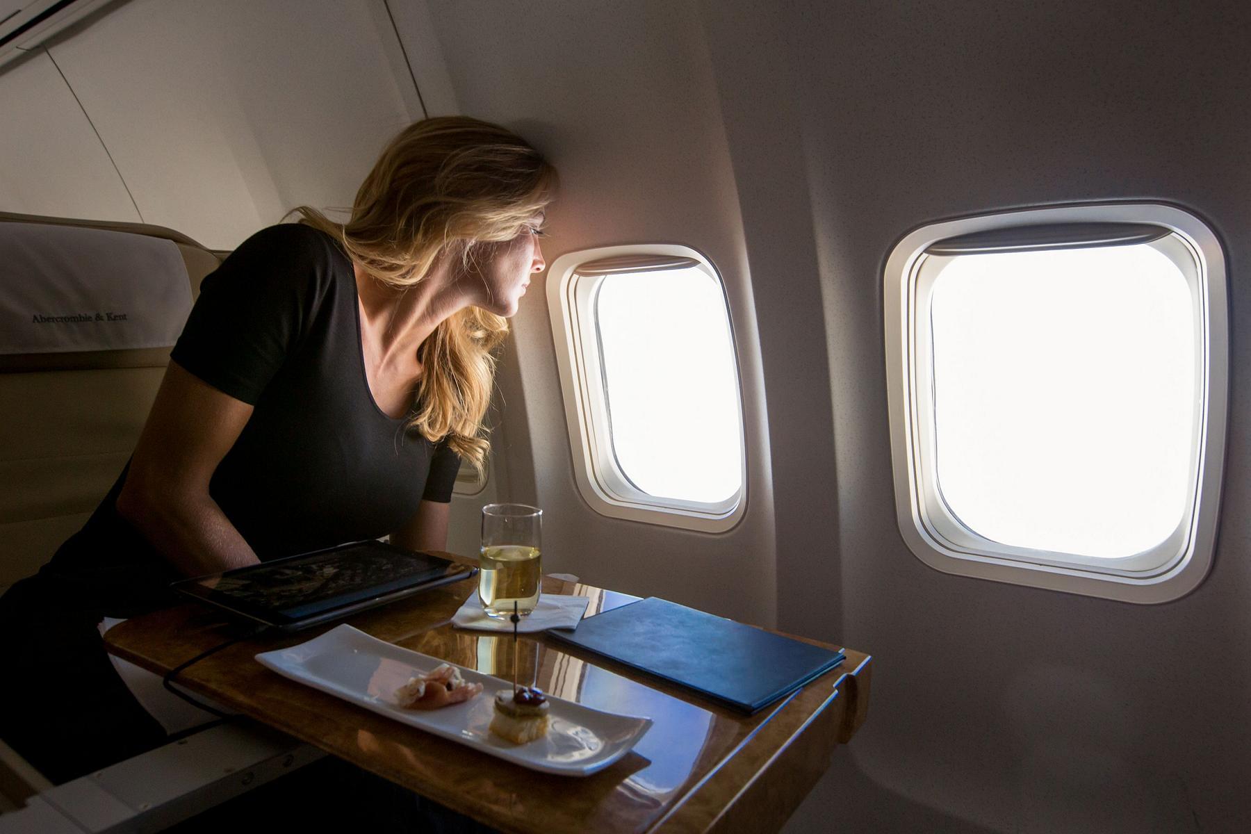 Frau mit Champagner schaut aus dem Fenster des Privatjets von Abercrombie & Kent