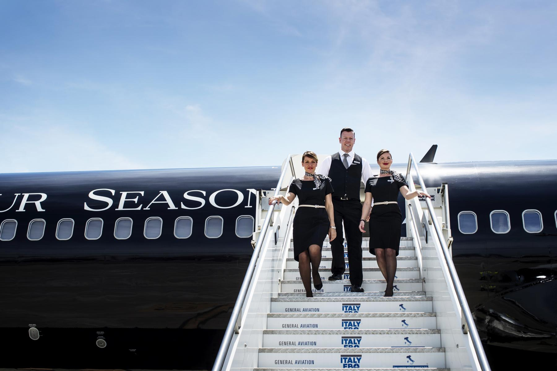 Die Crew des Four Seasons Private Jet vor dem Flugzeug auf der Treppe