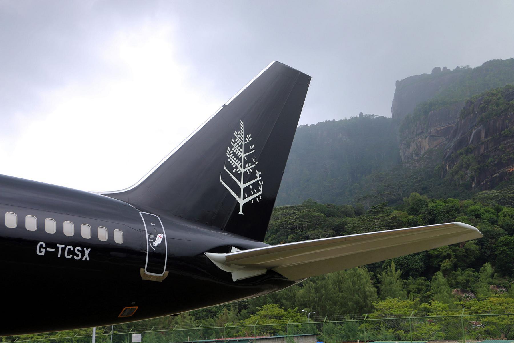 Der Heckflügel des Four Seasons Private Jet vor bewaldeten tropischen Bergen